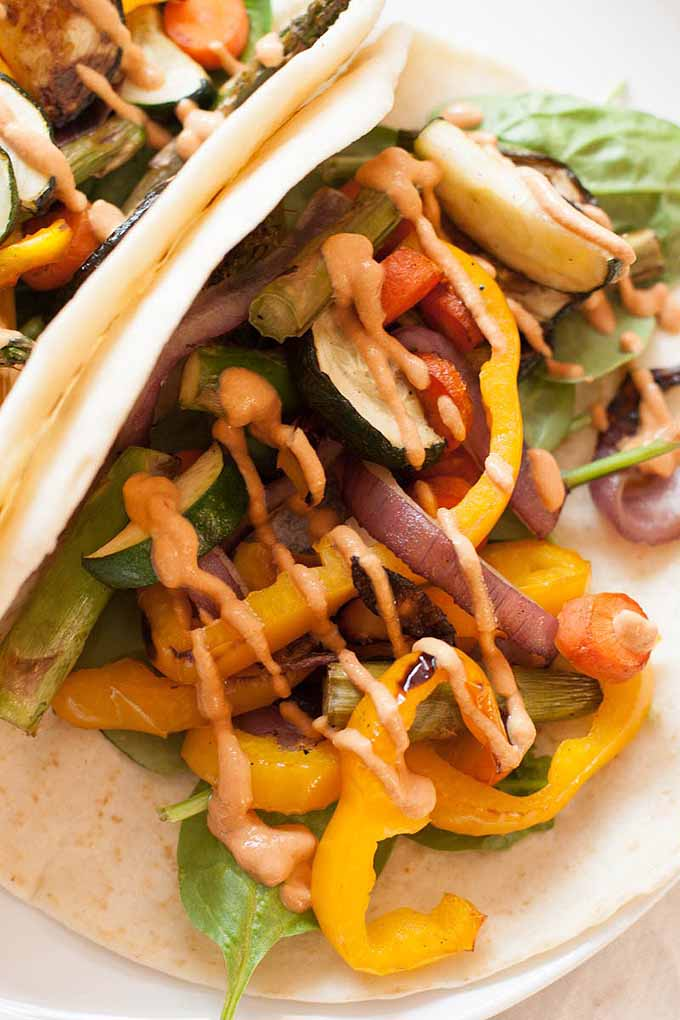 Close up view of two soft shell veggie tacos with a cashew-chipotle sauce.