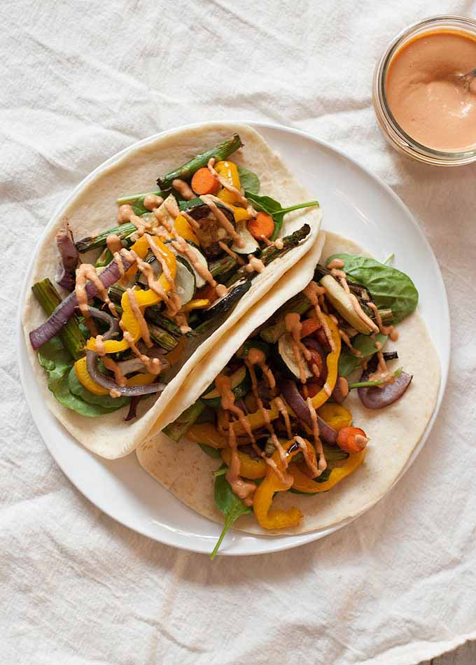 Top-down view of tortillas filled with grilled vegetables and topped with a pale orange-colored sauce.
