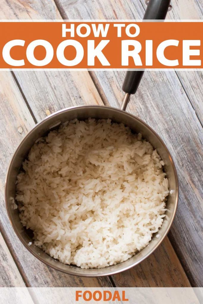 Top down view of a sauce pan full of fluffy cooked rice on a light toned wooden surface.