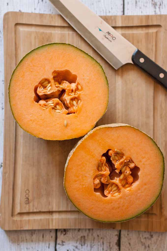 A halved cantaloupe with orange flesh rests on a wooden cutting board, next to a chef's knife, on a white distressed wood background.