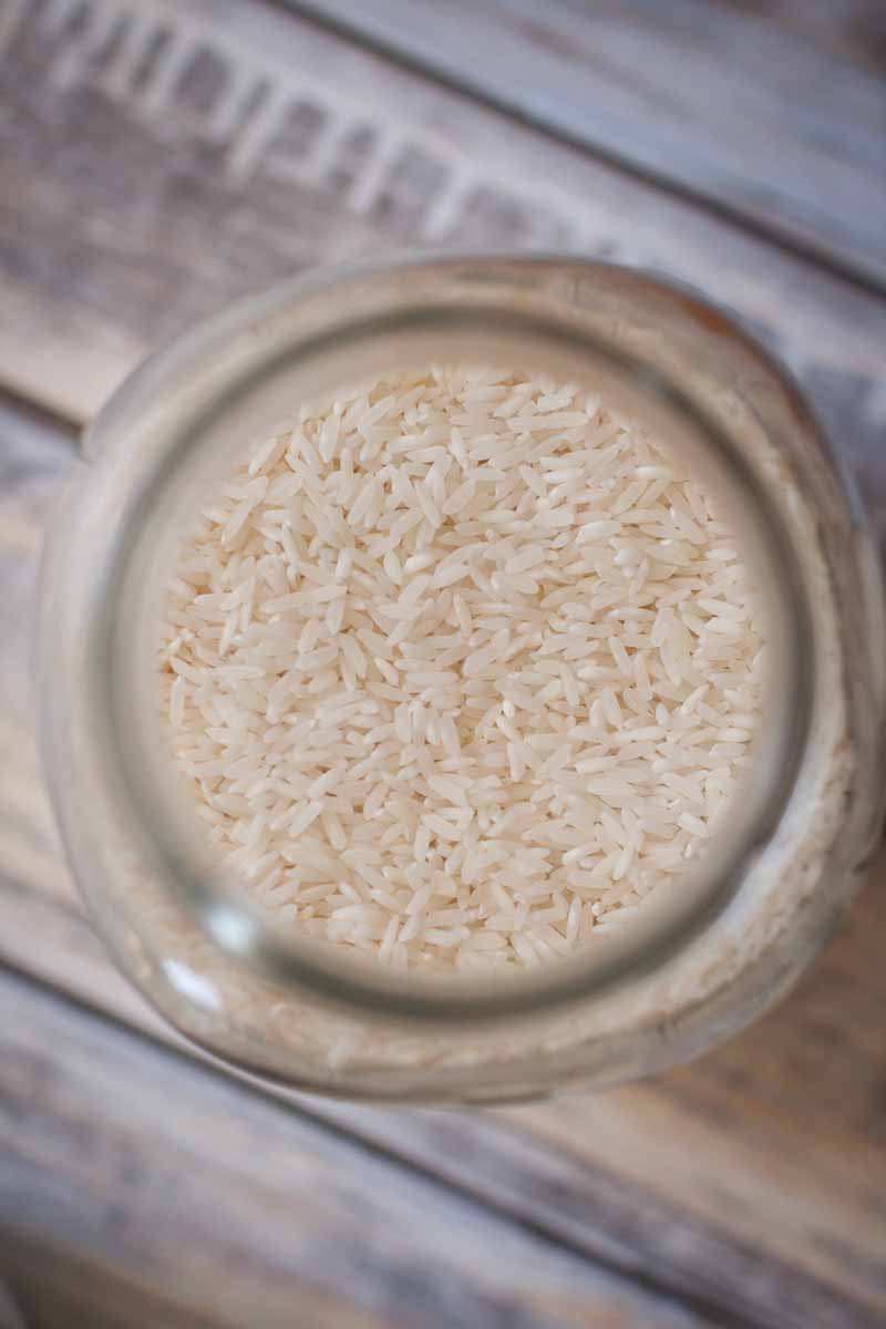 Top-down view of uncooked white rice in a glass mason jar.