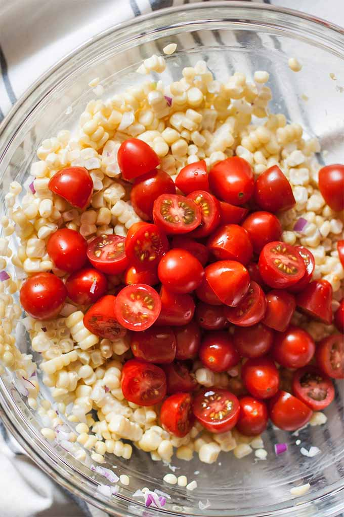 Top-down image of a large glass bowl of pale yellow corn kernels topped with halved red cherry tomatoes, on a blue and white striped cloth kitchen towel.