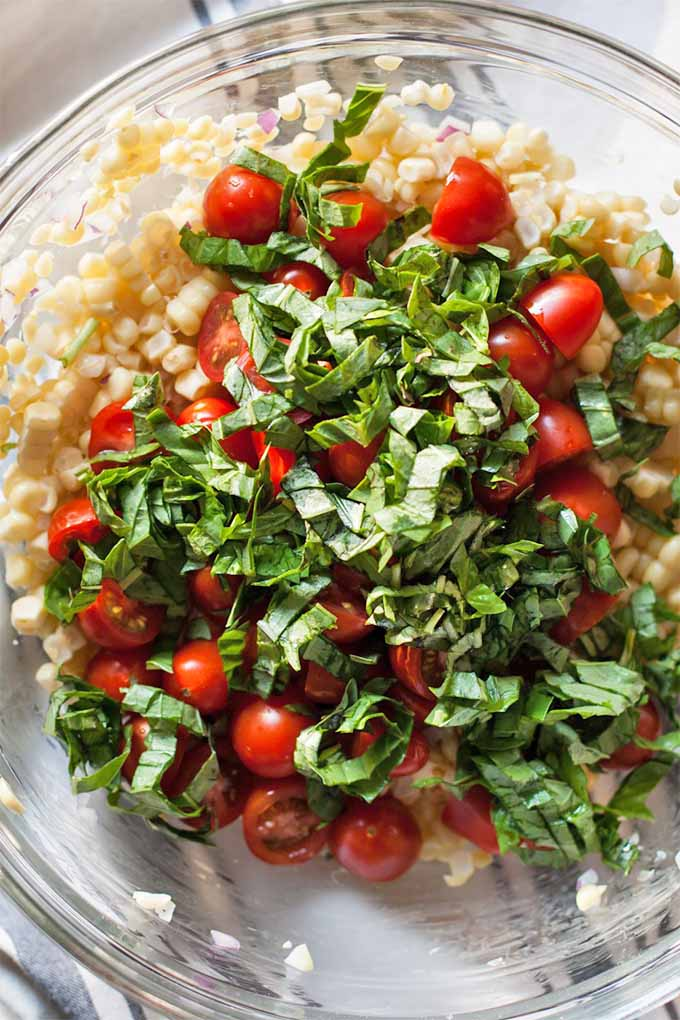 Top-down shot of a large glass mixing bowl with layered corn kernels, halved cherry tomatoes, and chopped green basil.
