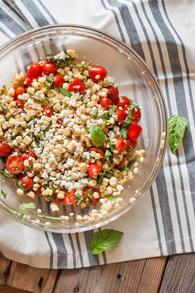 Top-down shot of a large glass mixing bowl filled with a corn and tomato salad with fresh herbs and topped with cheese, on a blue and white striped cloth with scattered basil leaves.