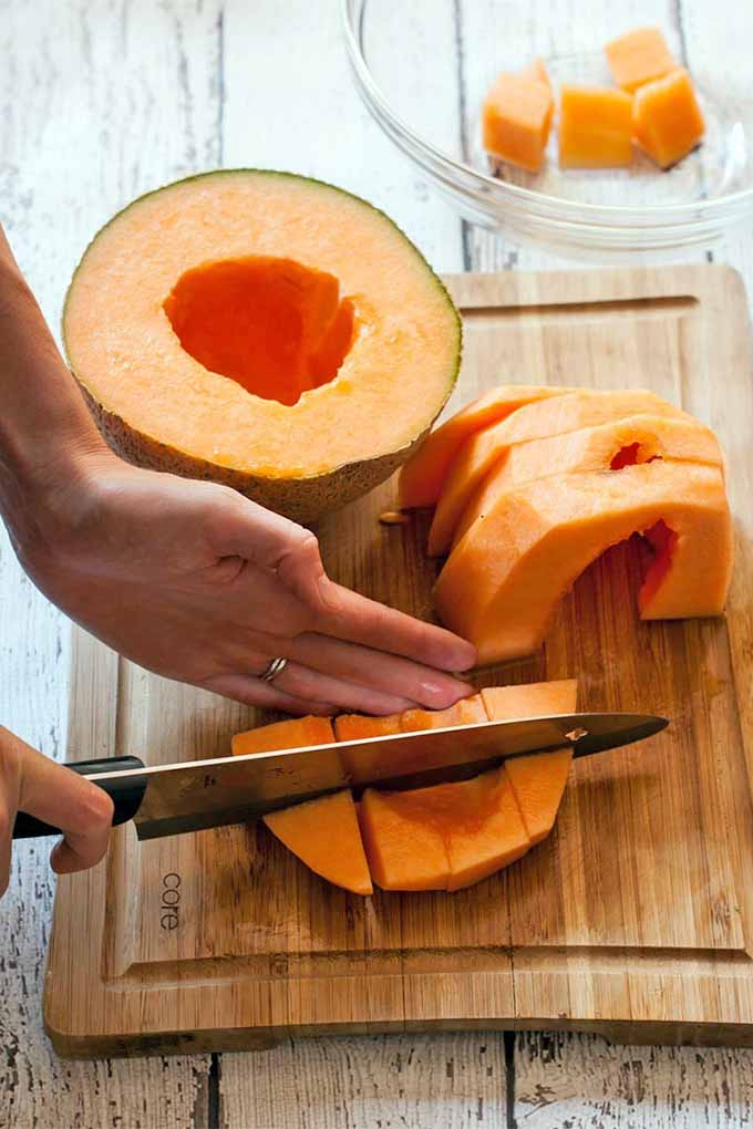 Closeup of a woman's hands cutting orange cantaloupe slices into chunks on a wooden cutting board, next to a glass bowl that is holding a few pieces of the fruit, on a white distressed wood surface.