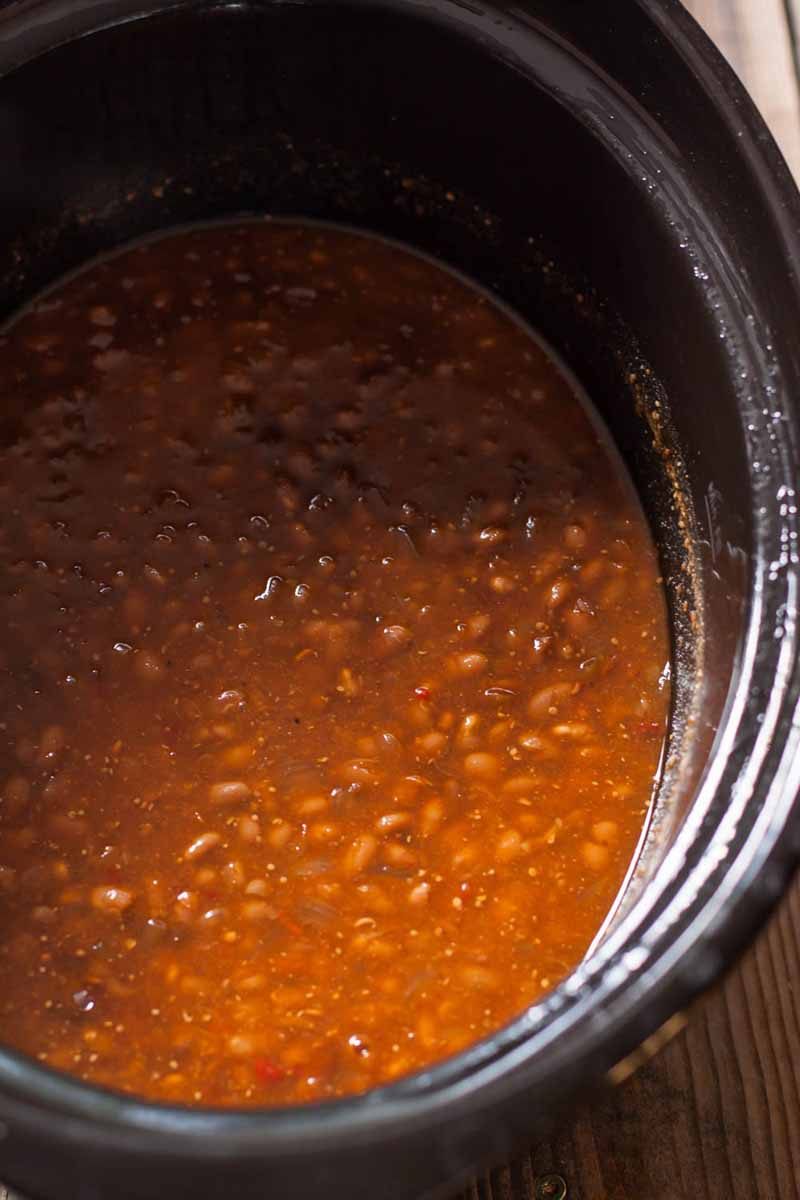 Close view of a vegetarian baked bean recipe inside of a slow cooker.