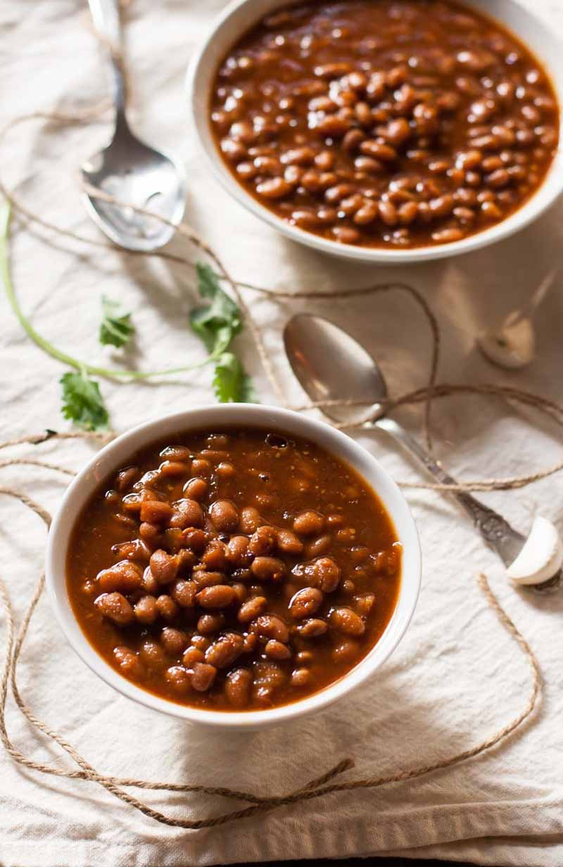 Two bowls of vegetarian slow cooker baked beans on white linen table cloth.
