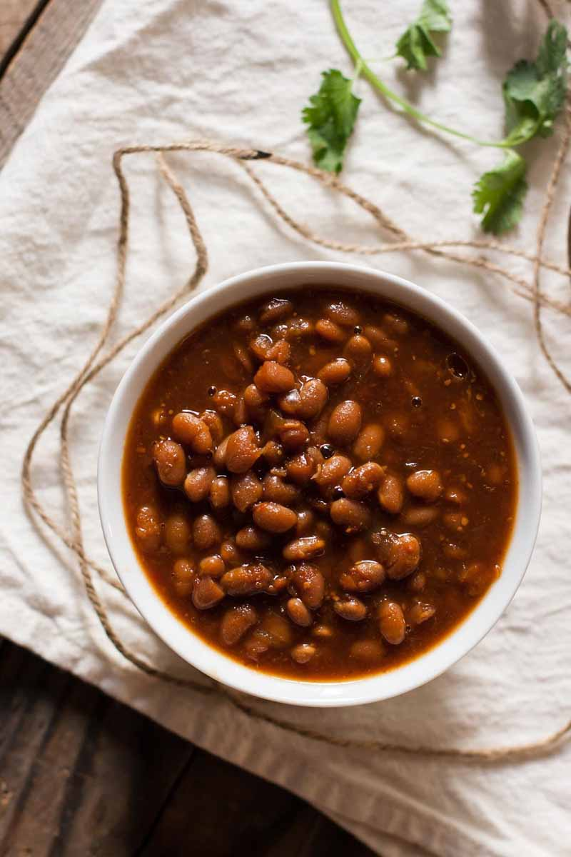 Top down view of a single white ceramic bowl full of vegetarian slow cooker baked beans.