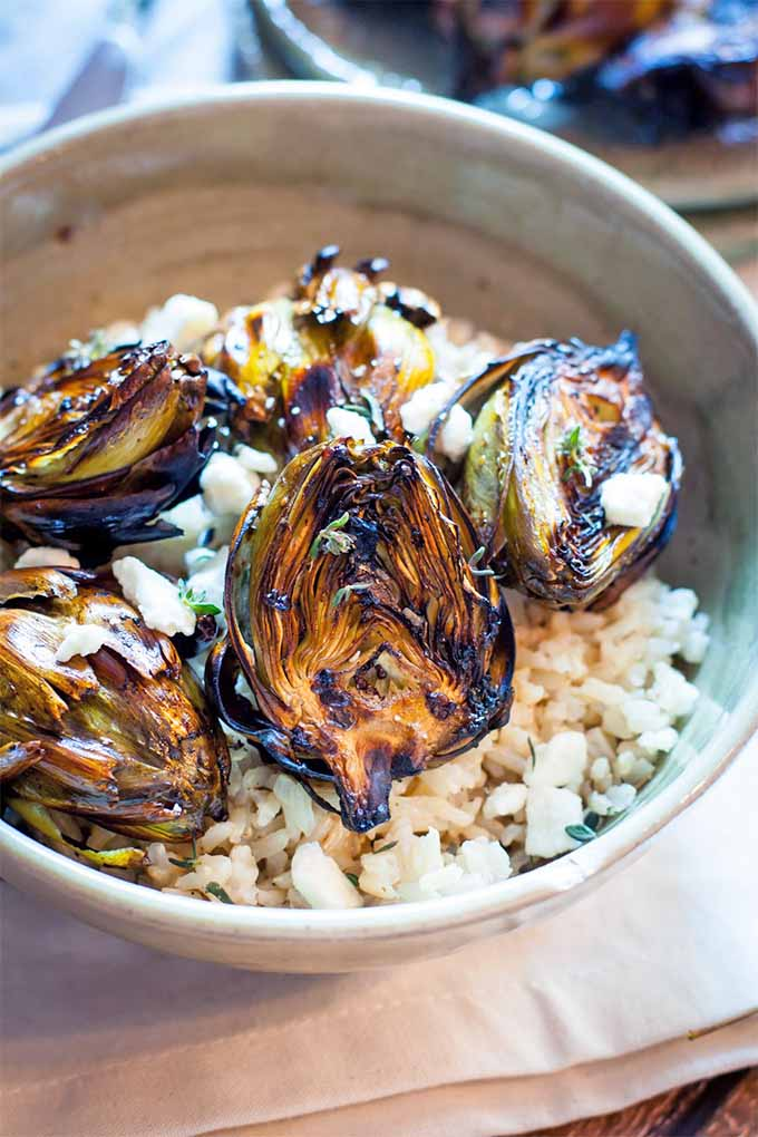 A gray ceramic bowl of grilled artichokes with brown rice and crumbled feta, on a folded cloth.