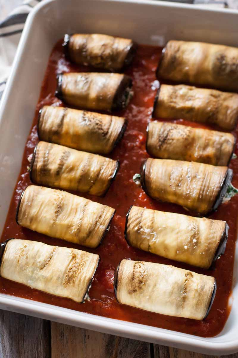 Unbaked Eggplant, Kale & Ricotta Cannelloni rolls in a white, porcelain baking dish surrounded by red marinara sauce.