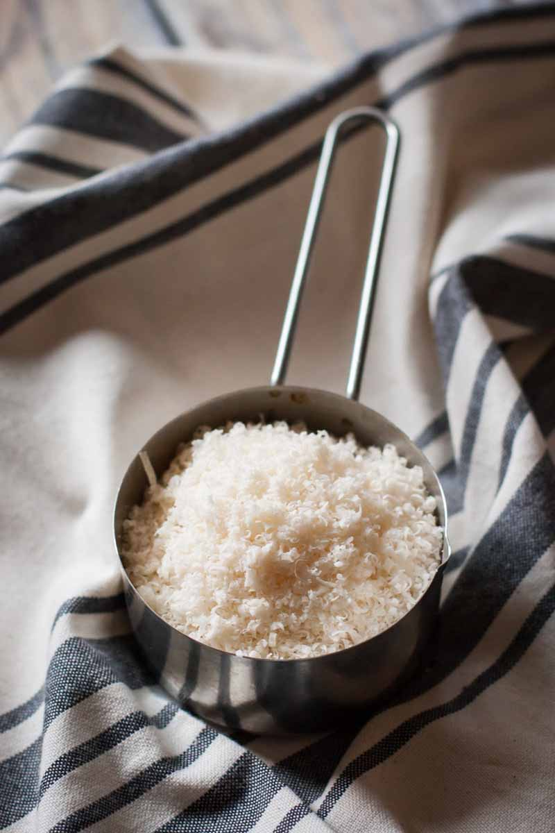 Close up of a stainless measuring cup full of freshly grated Parmesan cheese sitting on a blue and white dish towel.