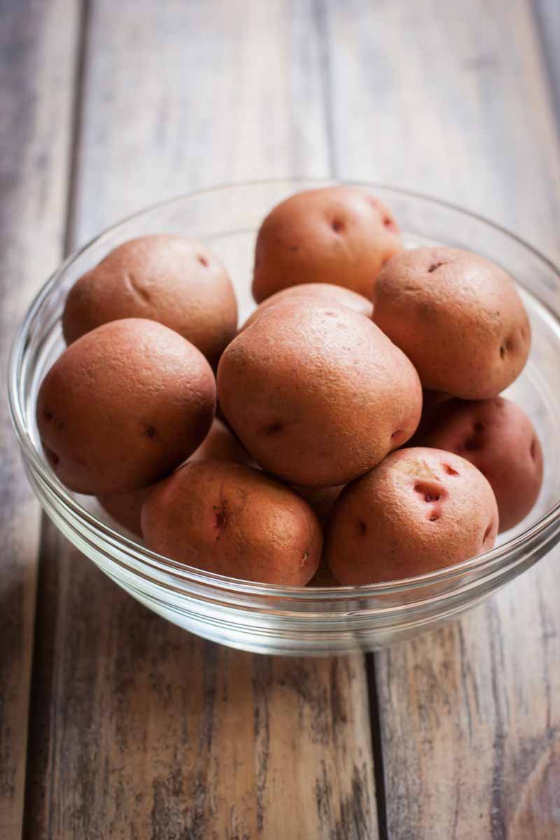 A glass mixing bowl full of small red potatoes sitting on a rustic wooden surface.