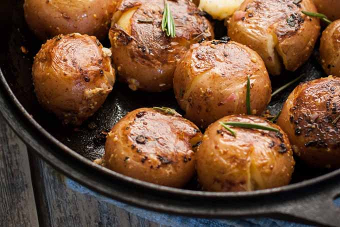 A close up of a batch of smashed red potatoes in cast iron frying pan.