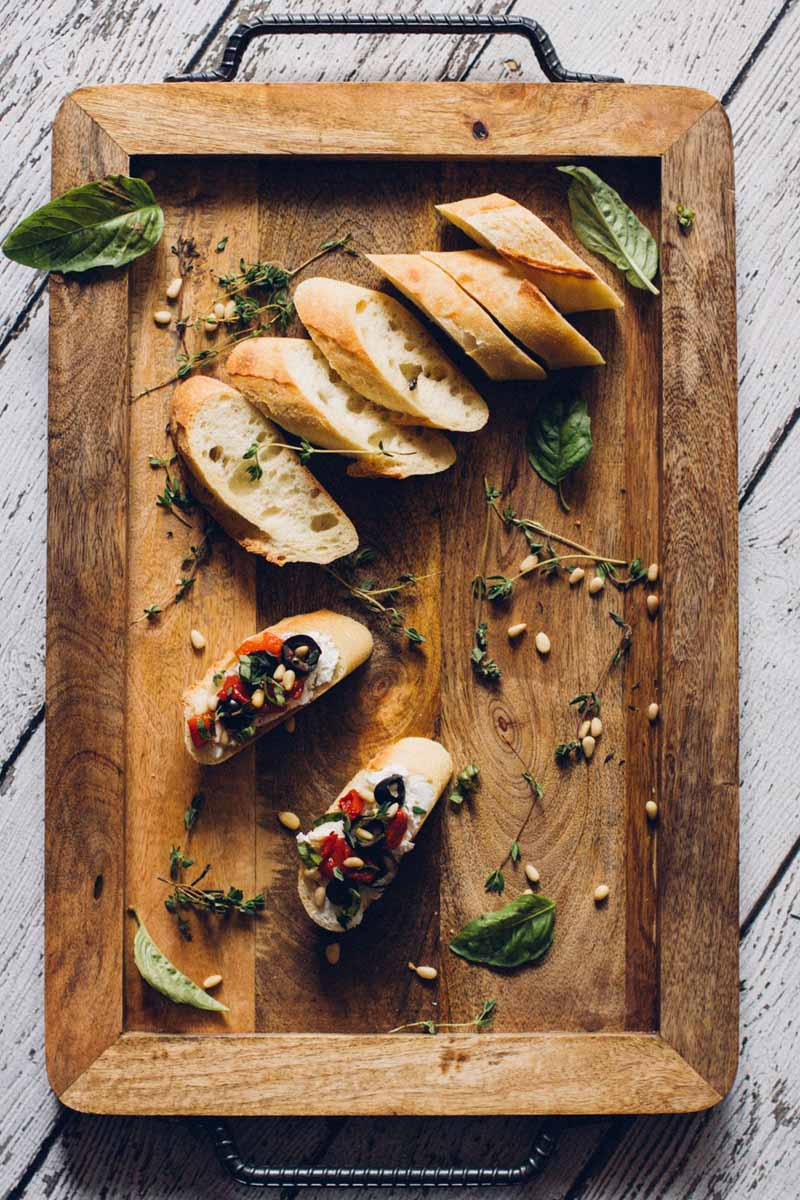 Top down view of a cutting board with slices of baguette and a couple of slices made into crostinis covered in black olives, red pepper, goat cheese, and pin nuts.