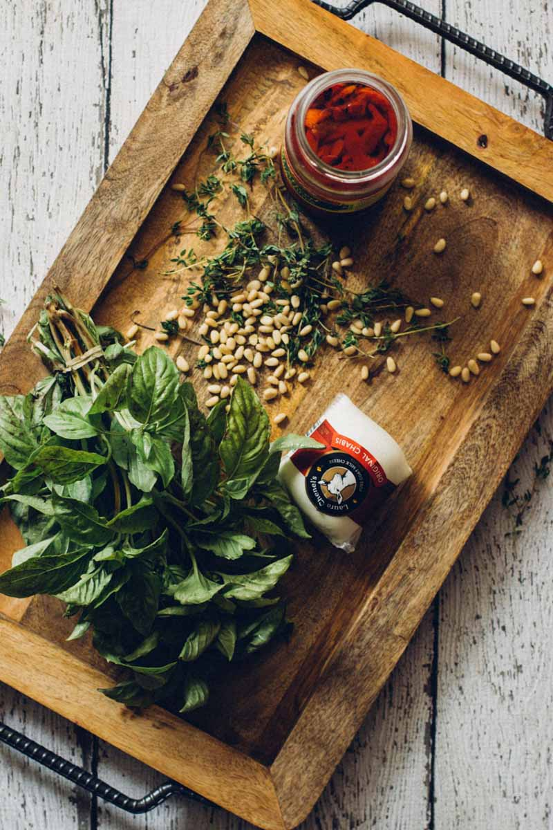 A wooden cutting board with a bunch of fresh basil, fresh thyme, a jar of roasted red pepper, and loose pine nuts scattered about.