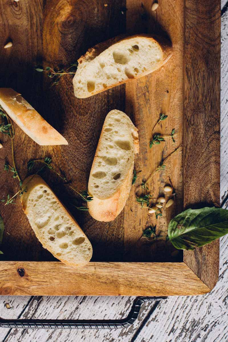 Top down view of slices of baguette bread, fresh basil leaves, fresh thyme, and loose pine nuts on a rustic wooden cutting board.