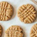 Top down view of five vegan peanut butter cookies on parchment paper