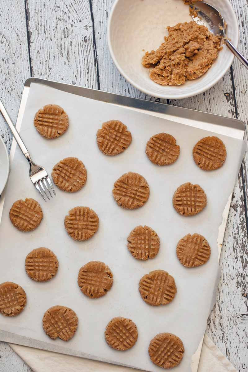Top down view of unbaked vegan peanut butter cookies laid out on a cookie sheet with a parchment sheet.