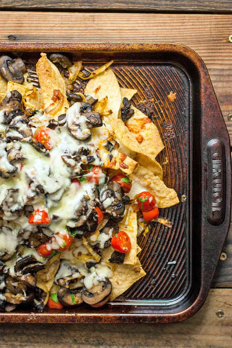 A brown sheet pan of yellow tortilla chips topped with melted cheese and vegetables, on a brown wooden table.