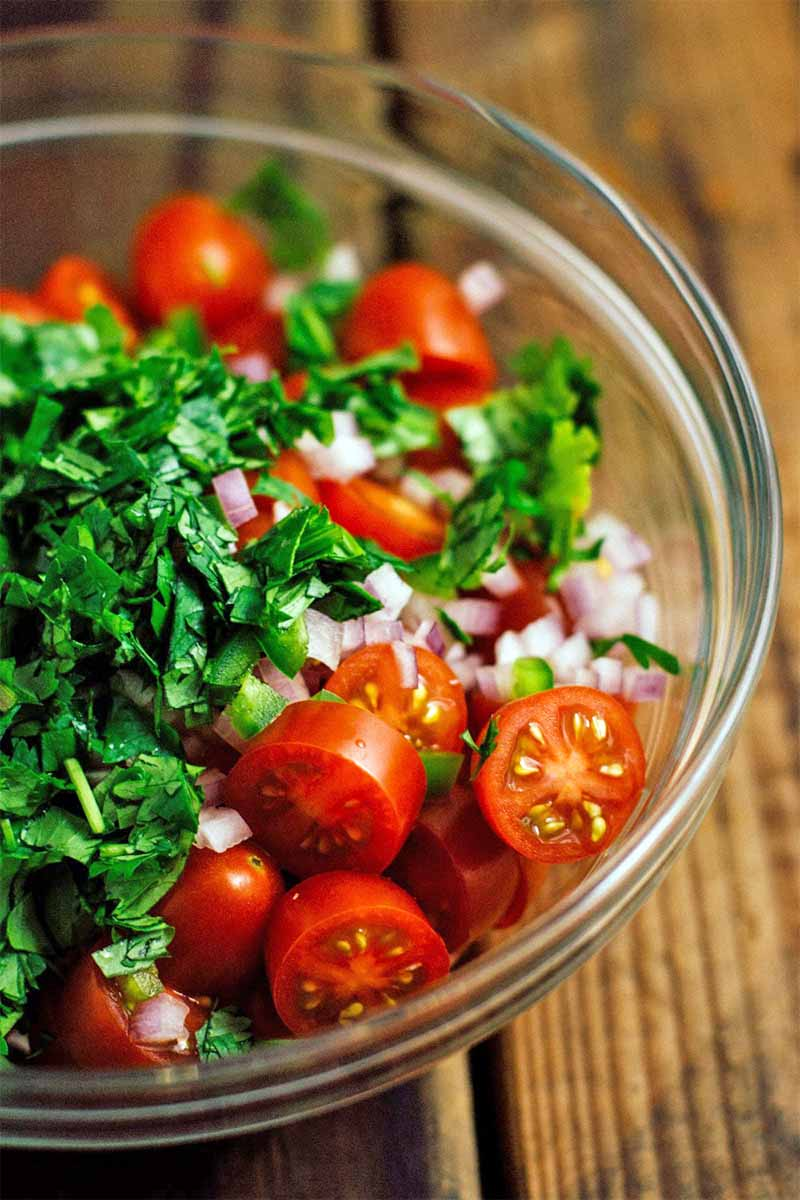 A glass bowl of tomatoes, chopped cilantro, and onion, on a brown wooden background.