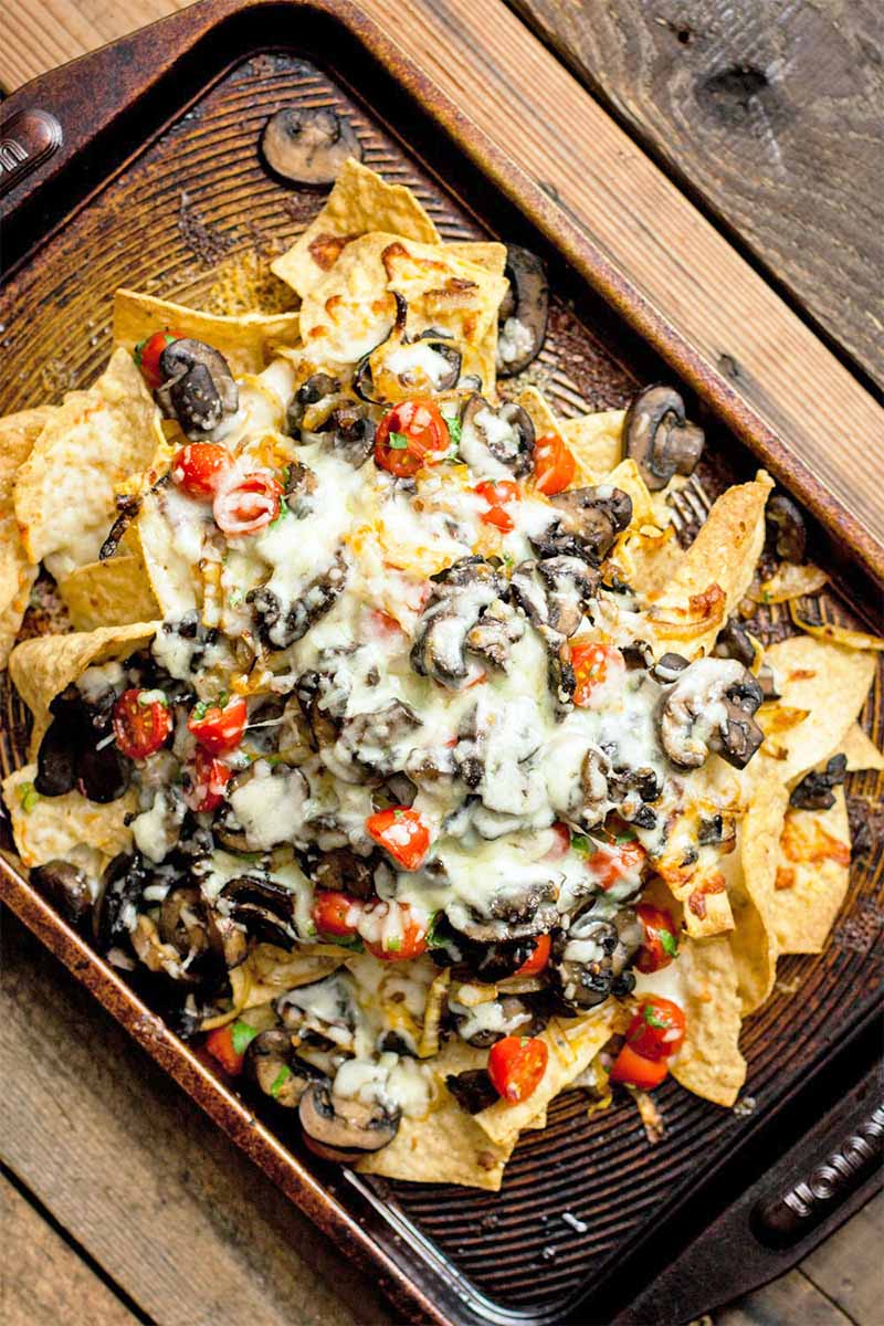Top-down shot of a baking sheet on a brown wood table arranged at an angle, topped with tortilla chips, vegetables, and melted cheese.