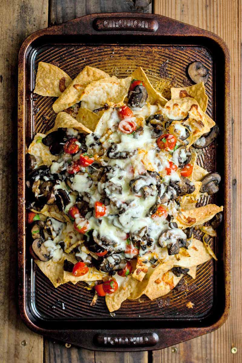 Top-down shot of tortilla chips topped with salsa, vegetables, and melted cheese, on a brown baking sheet, on a brown wood surface.