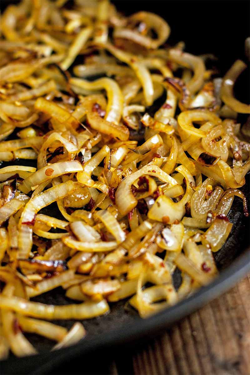 Seasoned onions caramelizing in a large frying pan, on a brown wood table.