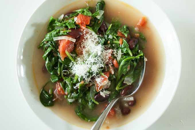 Top down view of a white, ceramic bowl full of Italian-Style Beans and Greens Soup.