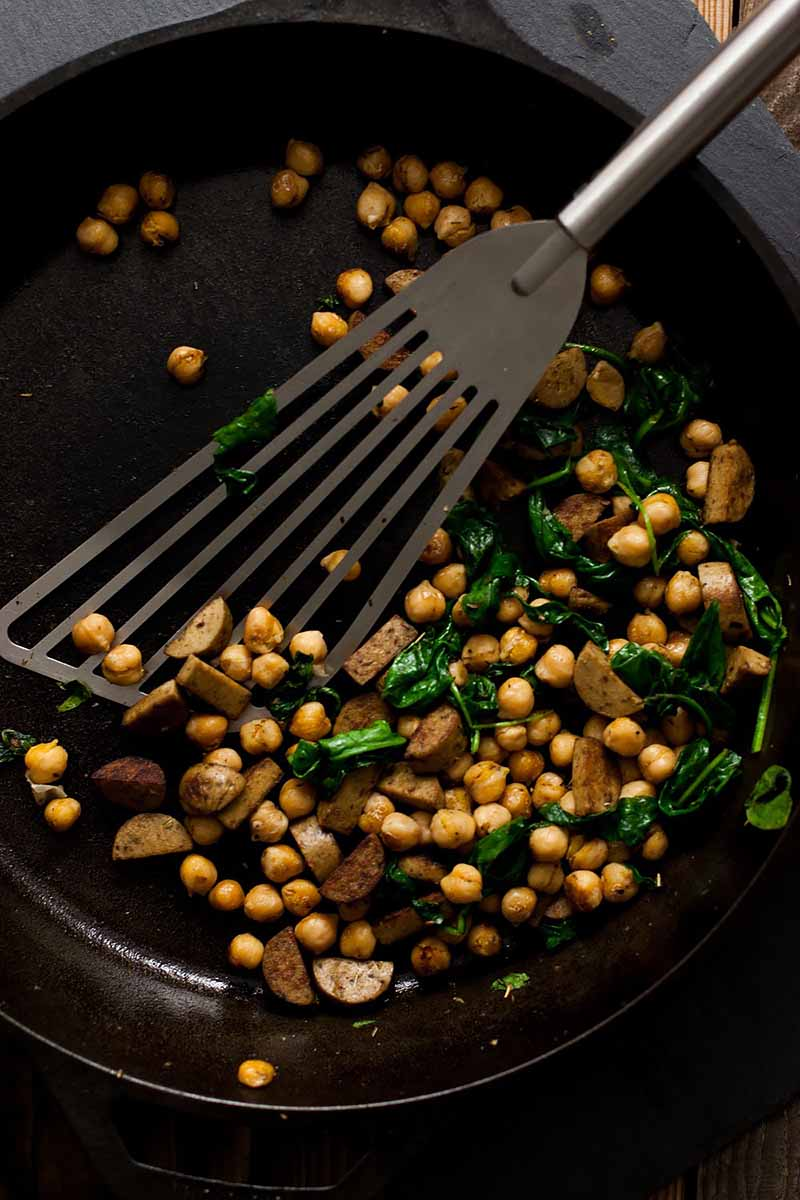 Vertical image of a spatula mixing beans, sausage, and spinach in a pan.
