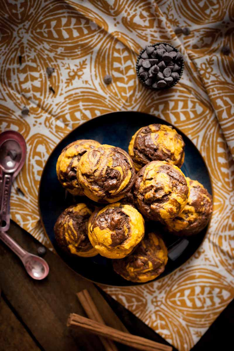 Top-down view of a dozen chocolate and squash puree swirl muffins on a black platter sitting on a cream and white tablecloth.