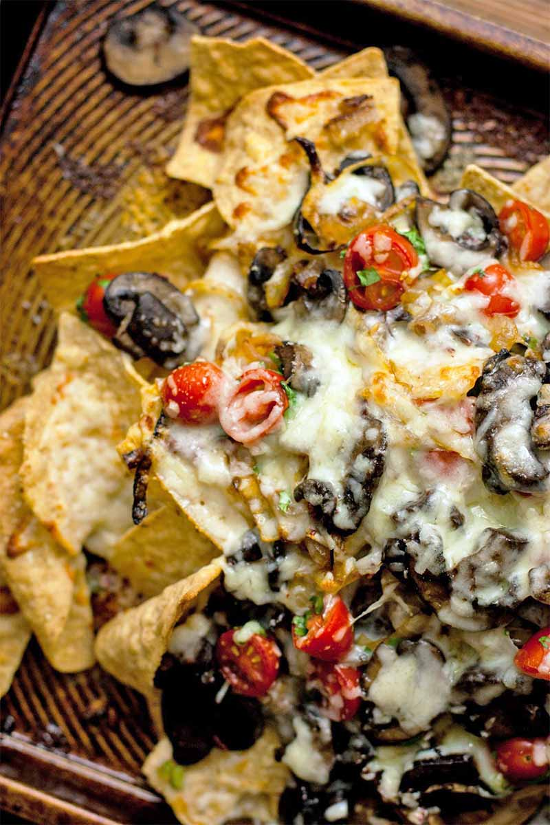 Closeup of homemade nachos on a brown sheet pan, with melted white cheese, mushrooms, onions, and cherry tomato salsa.