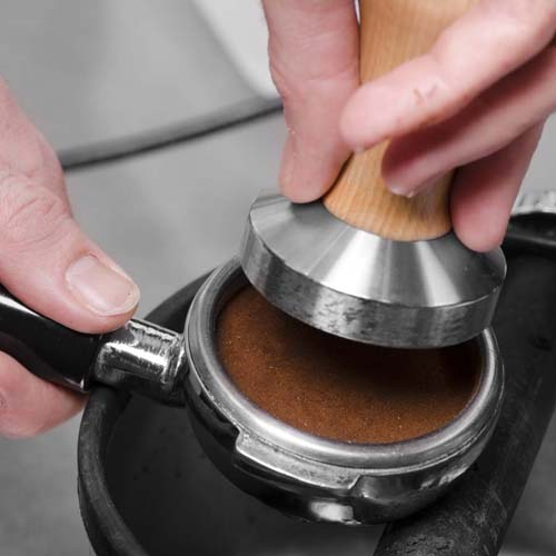 Tamping coffee grounds in portafilter basket | Foodal.com