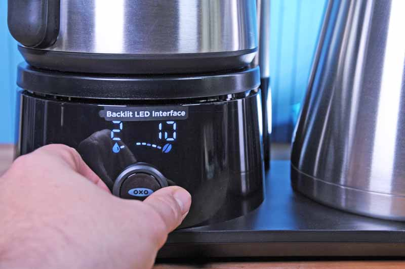 A human hand uses the control knob on the OXO On 12 Cup Brewing System to adjust the balance bewteen hot cups of water to remain in the kettle and how much that will be used to brew coffee.
