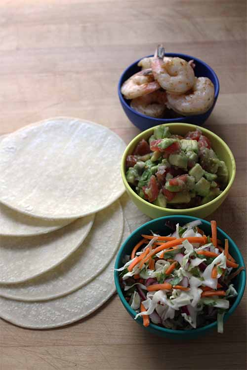 Set up your own taco buffet bar with grilled shrimp, cabbage slaw, fresh flour or corn tortillas, and avocado tomato salsa. We share the recipe: https://foodal.com/recipes/mexican-latin-america/shrimp-tacos/ 