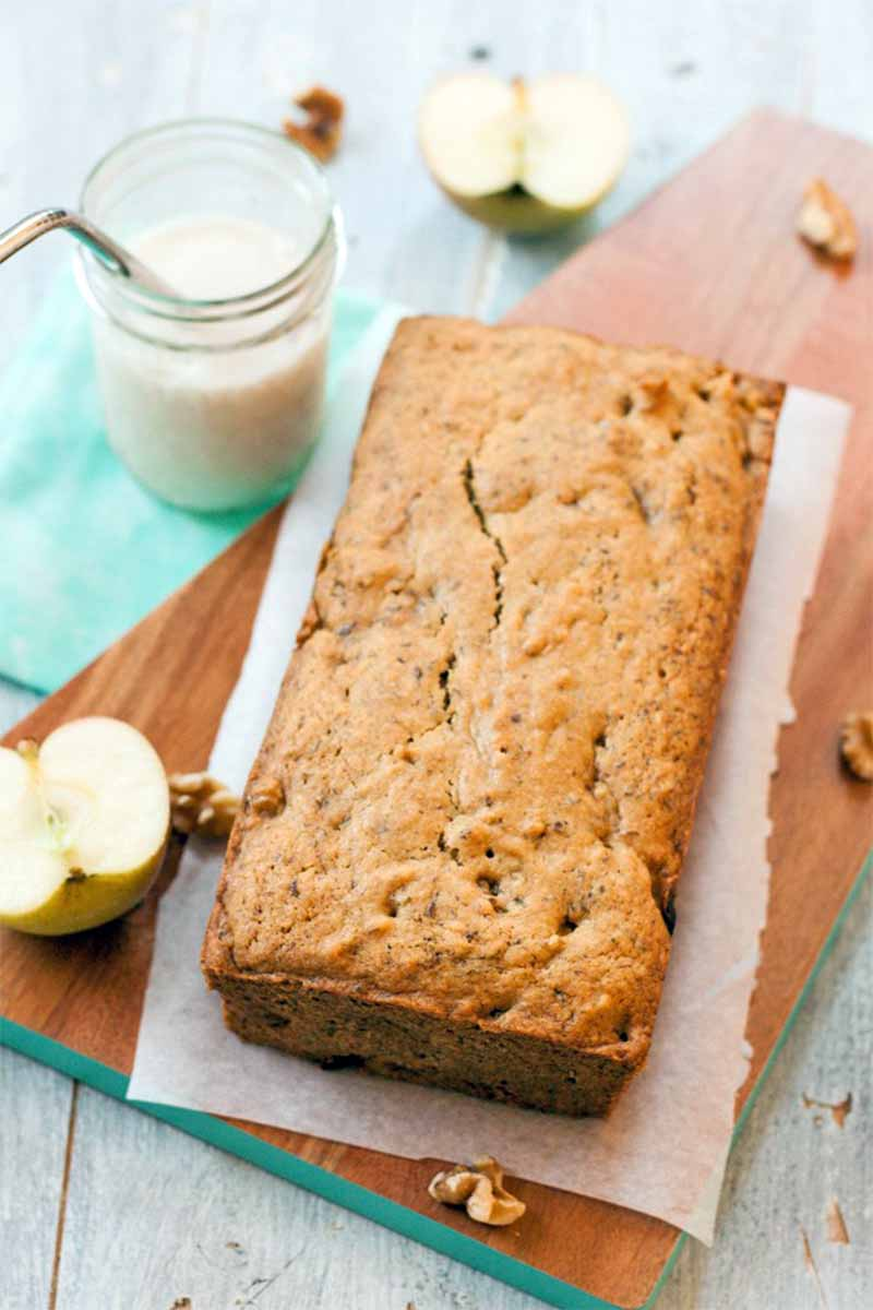 Top-down vertical shot of a loaf-shaped apple quick bread on a piece of parchment paper on top of a rectangular serving board, with sliced fruit, a jar of almond milk with a stainless steel straw, on a blue cloth background.