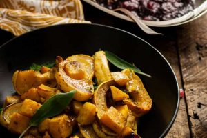 Close up of a pan of roasted Dijon sage flavored butternut squash with a pomegranate cranberry sauce in the background.
