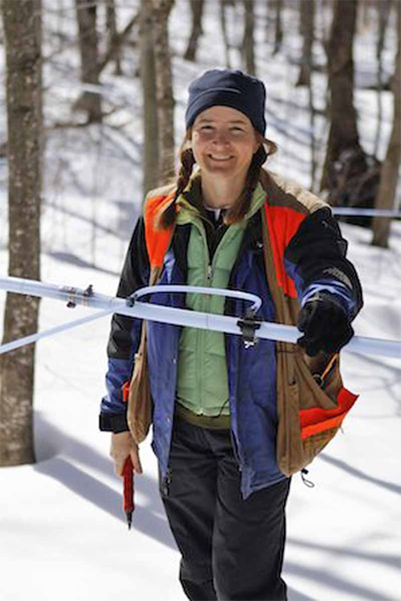 Laura Sorkin of Runamok Maple, wearing outdoor gear in snow surroundings with trees in the background.