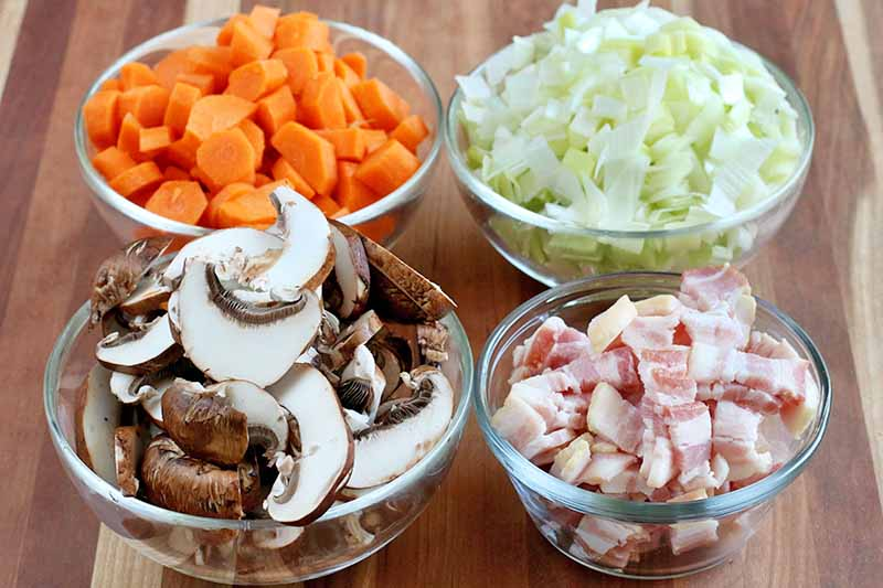 Four small glass bowls of chopped and prepped carrots, leeks, bacon, and crimini mushrooms, on a brown wood surface.