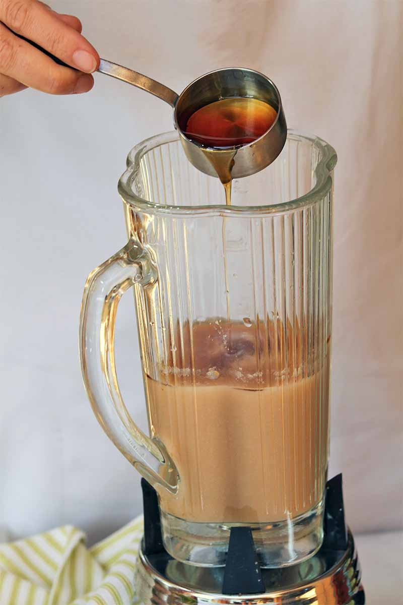A hand at the top left of the frame holds a metal measuring cup and pours the maple syrup that it contains into the glass blender canister below, which is filled partway with a light brown puree, on a gray background with a green and white striped kitchen towel at the base of the appliance.