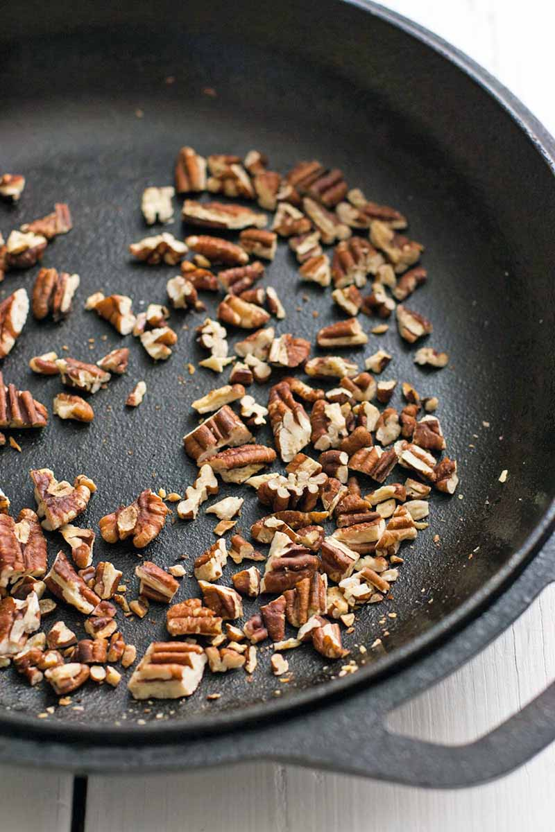 Chopped nuts toasting in a large, heavy frying pan.