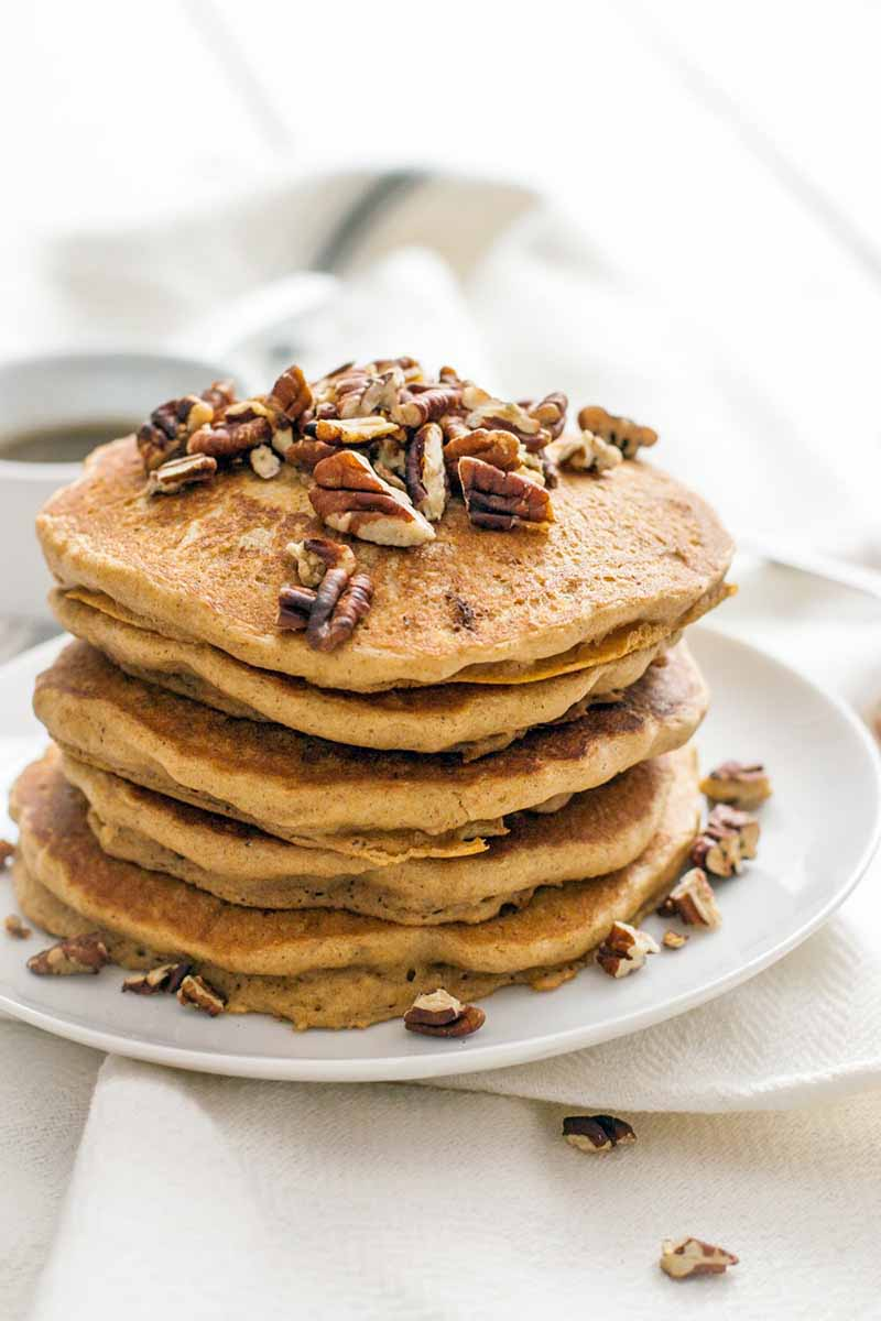 Six pancakes topped and surrounded by chopped pecans are stacked on a white plate, on a surface topped with a wrinkled white cloth.