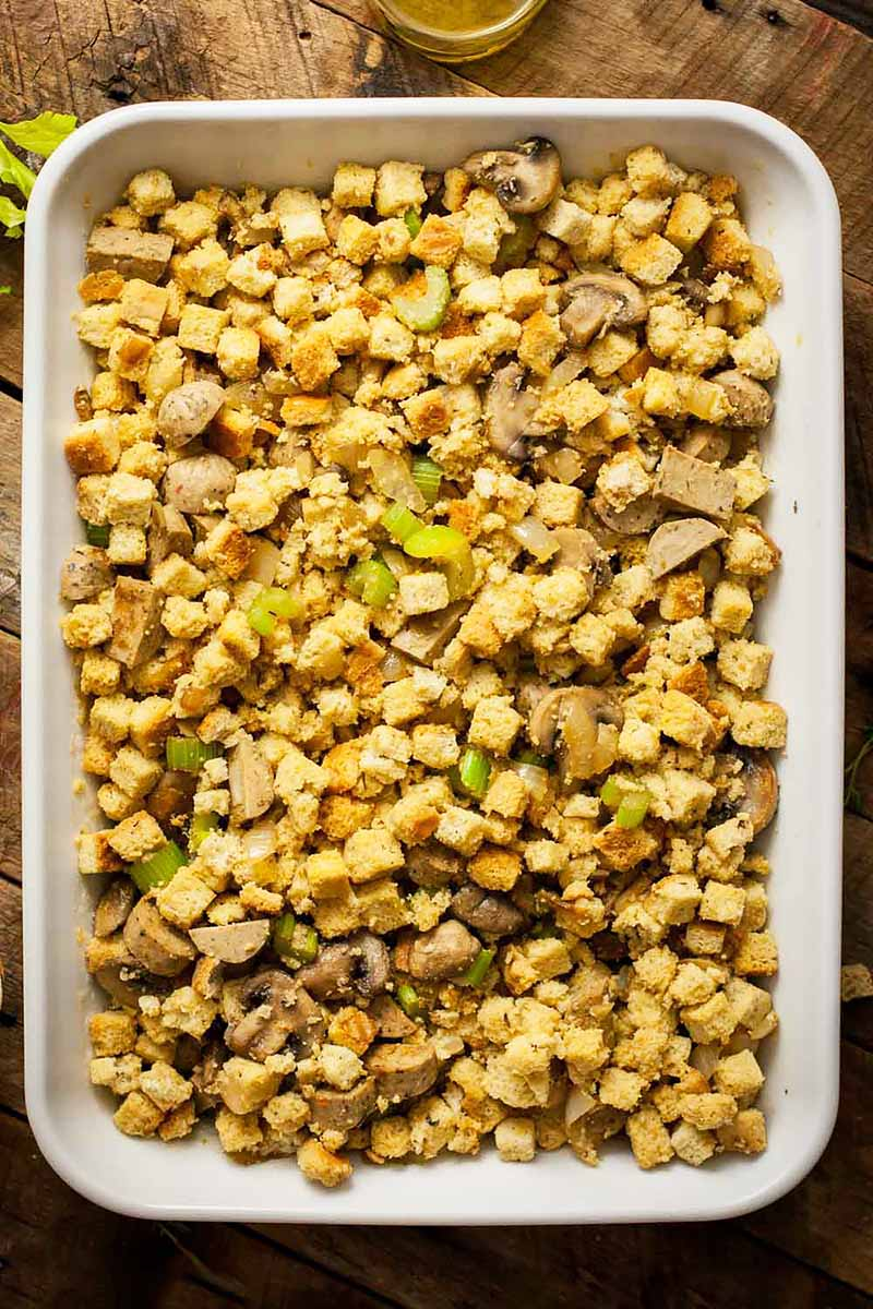 Vertical top-down image of a casserole dish filled with stuffing and vegetables.