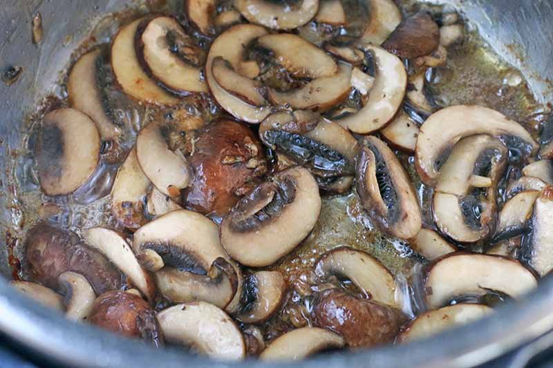 Sliced mushrooms are sauteeing in a metal Instant Pot insert.
