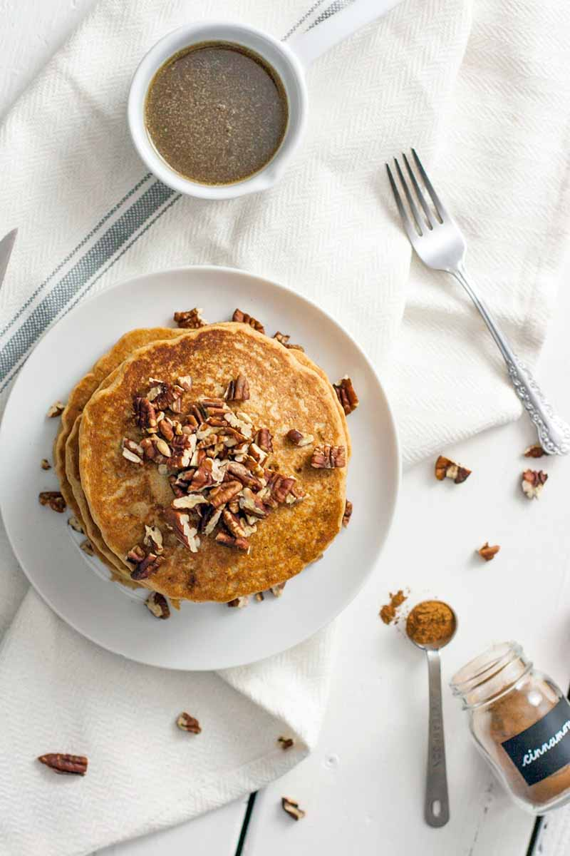 Overhead shot of pancakes topped with pecans on a white plate, on top of a white kitchen towel with a blue stripe, with a small white dish of brown sugar syrup, a fork, a container and measuring spoon full of cinnamon, and scattered nuts.