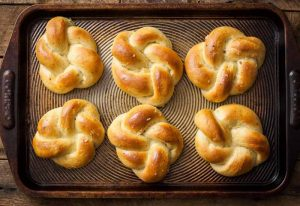 Horizontal top down view of six knot shaped vegan-friendly roasted garlic and herb dinner rolls sitting on a blackened baking pan.