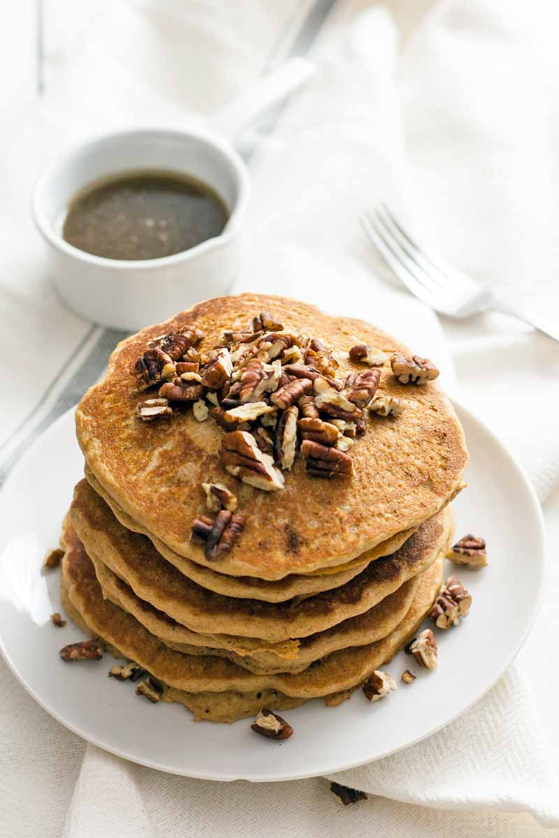 Oblique overhead shot of a stack of vegan pancakes topped with toasted pecans, on a white plate beside a white ramekin of brown sugar syrup, on a white cloth with a blue stripe, with a fork to the right of the frame, on a white background.