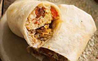 A close up of a vegetarian breakfast burrito cut in half with the insides showing.