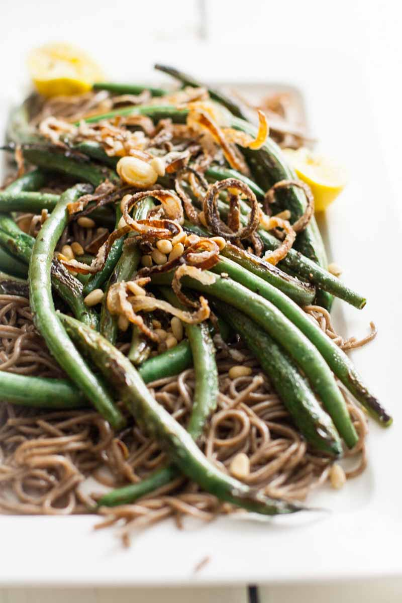 Oblique view of a vegan-friendly and gluten-free side dish made with green beans, buckwheat soba noodles, and shallots in a white rectangular serving dish.