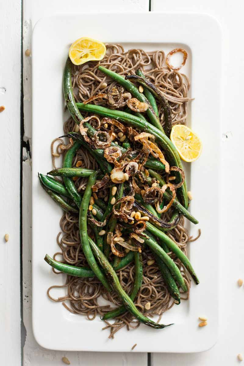 Top down view of a green bean and soba noodle side dish on a rectangular white serving platter on a white rustic wooden table.