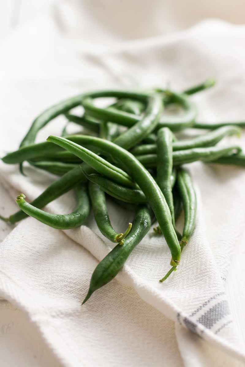 Fresh green beans on a white cloth napikin.
